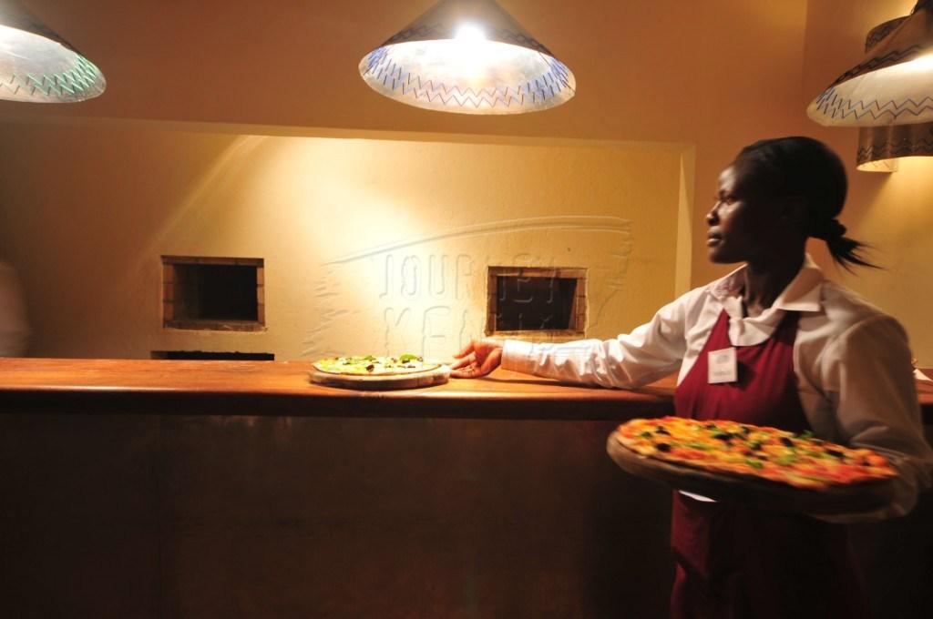 A waitress serving pizza at Acapulco Restaurant in Nairobi